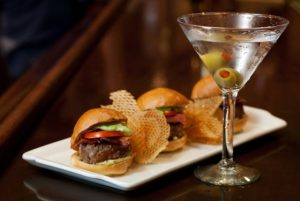An attractive presentation of sliders, chips and a martini. Courtesy of Palm Restaurant.