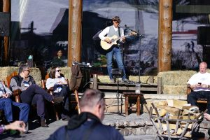 An individual performer sets the stage for an acoustic après ski on a sunny patio. Photo by Jensen Sutta.