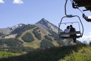 Bride and groom on a summer chairlift ride up to a mid-mountain wedding venue. Courtesy Crested Butte Mountain Resort.